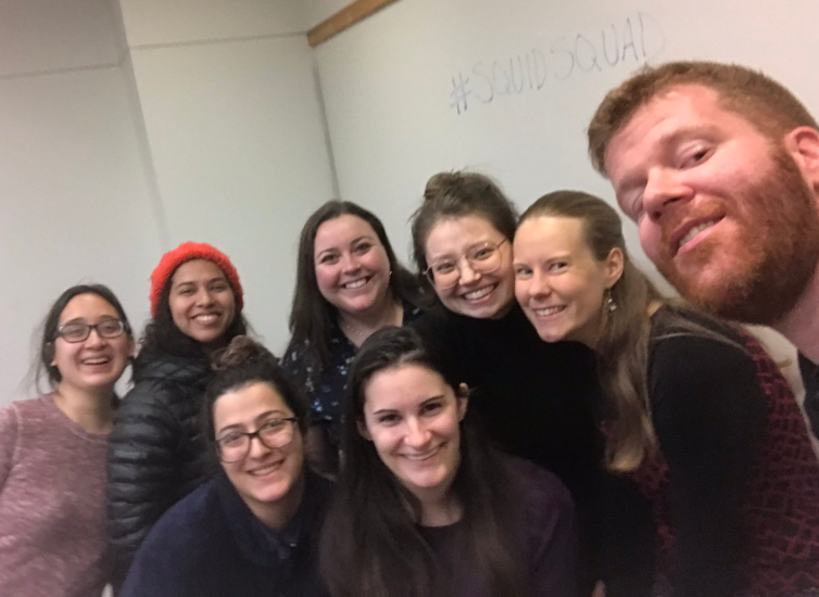 Group of scientists smiling with a whiteboard behind them that says #SquidSquad.