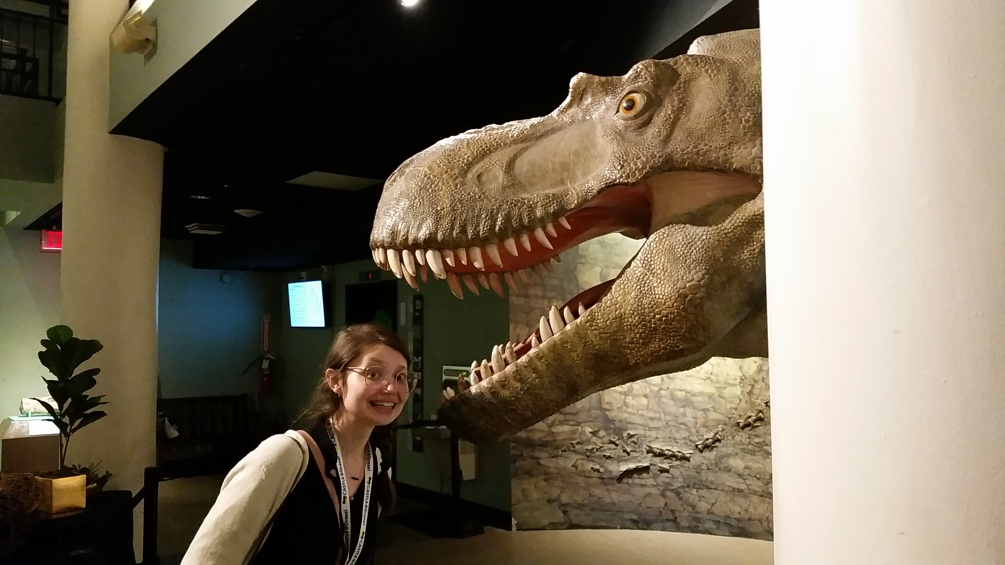 Cait standing beneath an open-mouth dinosaur model looking very scared.